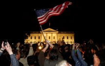 People cheer and wave U.S. flags outside the White House as President Barack Obama delivers remarks to the nation on the death of Al Qaeda leader Osama Bin Laden, in Washington