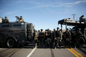 Police in riot gear watch protesters in Ferguson, Mo. on Wednesday, Aug. 13, 2014. On Saturday, Aug. 9, 2014, a white police officer fatally shot Michael Brown, an unarmed black teenager, in the St. Louis suburb. (AP Photo/Jeff Roberson)